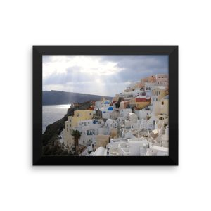 Sun Rays Fall on the Famous Village of Oia on the Greek island of Santorini in this Framed Poster