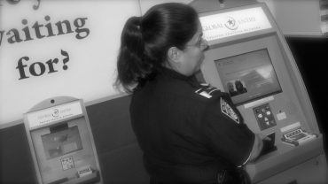 Photo from DHS of a Customs and Border Agent at a Global Entry Kiosk